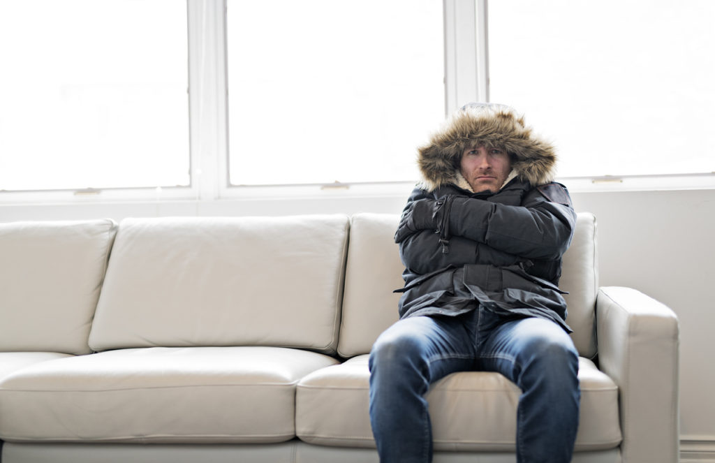 Man With Warm Clothing Feeling The Cold Inside House on the sofa