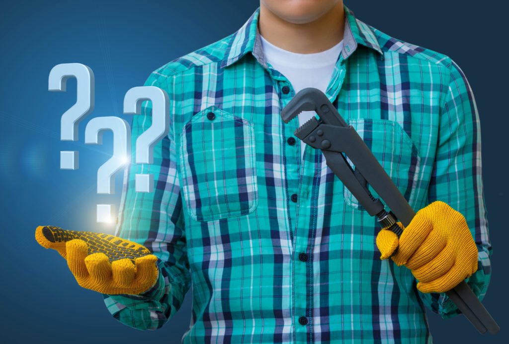 Plumber answers questions. Worker on a blue background with a spanner and questions in hand.